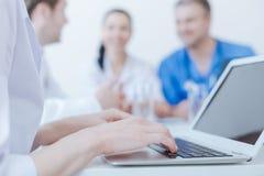 Bekwame medische specialist die digitaal gadget gebruiken op het werk royalty-vrije stock afbeeldingen