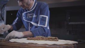 Bekwame mens in blauwe chef-kok eenvormige het koken lulakebab in modern restaurant De kok zet bovenste laagje op het geroosterde stock video