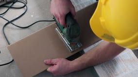 Bekwame mens die houten gelamineerde raad met elektrische kaliberzaag zagen stock videobeelden