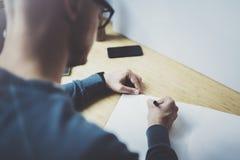 Bekwame ontwerper Kaukasische mens die abstracte schets met pen trekken Het proces van het kunstwerk Creatieve hobby Het nota nem royalty-vrije stock foto