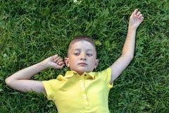 Bekymmerslös caucasian pojke i den gula skjortan som ligger på gräset royaltyfri foto