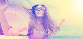 Bekymmerslös dans för ung kvinna i solnedgången på stranden royaltyfri fotografi