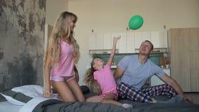 Bekymmerslös familj i pyjamas som tillsammans spelar på säng arkivfilmer