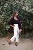 Bekymmerslös flicka för lycklig boho med buketten av vildblommor som ler och går i aftonsommarbygd Stilfull bohemisk flicka med royaltyfri bild