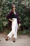 Bekymmerslös flicka för lycklig boho med buketten av vildblommor som ler och går i aftonsommarbygd Stilfull bohemisk flicka med arkivbild