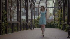 Bekymmerslös flicka som talar på telefonen, medan gå utomhus lager videofilmer
