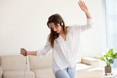 Bekymmerslös kvinna i hörlurar som dansar till musik som spelar på smartph arkivfoton