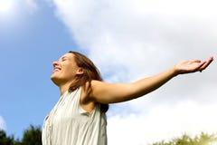 Bekymmerslös kvinna som ler med öppen armspridning royaltyfria bilder
