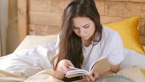 Bekymmerslös kvinna som ligger på en säng med boken stock video