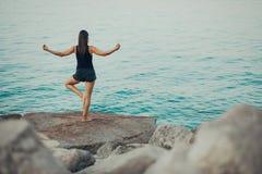 Bekymmerslös kvinna som mediterar i natur Finna inre fred Man att göra hälften som viker i sittande lotusblommapos Andlig läka li royaltyfri foto