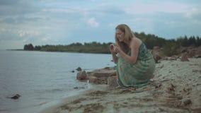 Bekymmerslös kvinna som samlar havsstenar på stranden arkivfilmer