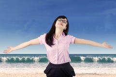 Bekymmerslös kvinna som tycker om frihet på stranden royaltyfri bild