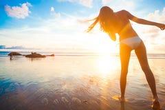 Bekymmerslös kvinnaspring i solnedgången på stranden sunt bosatt begrepp för semestervitalitet Bevattna tappar arkivfoto