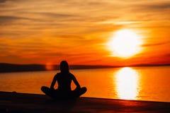 Bekymmerslös lugna kvinna som mediterar i natur Finna inre fred Man att göra hälften som viker i sittande lotusblommapos Andlig l royaltyfri foto