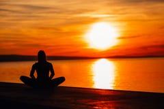 Bekymmerslös lugna kvinna som mediterar i natur Finna inre fred Man att göra hälften som viker i sittande lotusblommapos Andlig l arkivbilder