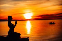 Bekymmerslös lugna kvinna som mediterar i natur Finna inre fred Man att göra hälften som viker i sittande lotusblommapos Andlig l royaltyfria foton