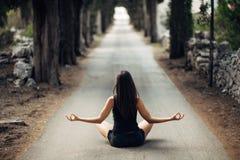 Bekymmerslös lugna kvinna som mediterar i natur Finna inre fred Man att göra hälften som viker i sittande lotusblommapos Andlig l arkivbild