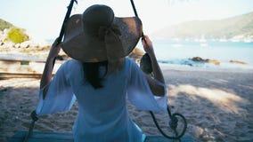 Bekymmerslös lycklig kvinna i hatt på gunga på den härliga paradisstranden i Thailand stock video