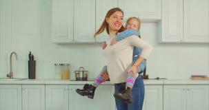 Bekymmerslös moder som piggybacking den upphetsade ungen i kök arkivfilmer