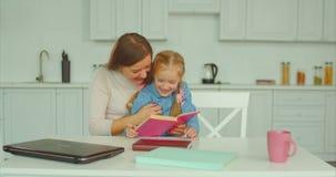 Bekymmerslös mum- och dotterläsebok i kök arkivfilmer