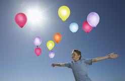 Bekymmerslös pojke i Midair med färgrika ballonger royaltyfria bilder