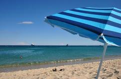 Bekymmerslös semester: randigt strandparaply, badskor på sanden och ljust blått hav arkivbilder