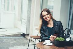 Bekymmerslös tid i kafé Attraktiv ung kvinna med ett leendesammanträde i det utomhus- kafét och snabbt meddelande för maskinskriv Arkivbild