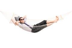 Bekymmerslös ung affärsman som ligger i en hängmatta Arkivbild