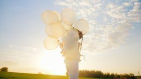 Bekymmerslös ung kvinna med ballonger som går på en grön äng på solnedgången Begrepp - lightness och rörelsefrihet stock video