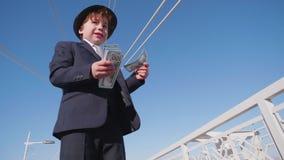 Bekymmerslös ung pojke som kastar pengarkassa från sikt för låg vinkel för bro Den unga pojken ser som affärsmanavfallspengar på stock video