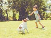Bekymmerslös unge och älsklings- hund som spelar med flygsåpbubblor på den soliga sommardagen Arkivfoto