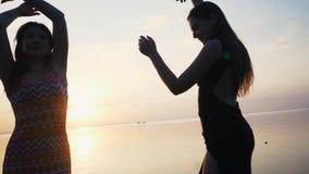 Bekymmerslösa kvinnor i lång svart klänningdans på stranden på solnedgången arkivfilmer