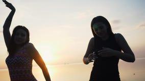 Bekymmerslösa kvinnor i lång svart klänningdans på stranden på solnedgången stock video
