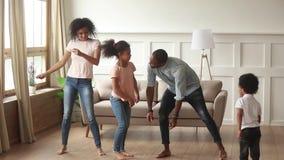 Bekymmerslösa svarta föräldrar och ungar som tillsammans dansar i vardagsrum arkivfilmer