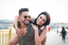 Bekymmerslösa unga caucasian par i staden som gör ridtur på axlarna på det fria arkivfoton