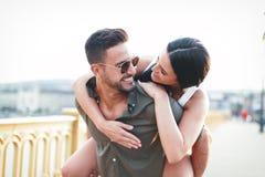 Bekymmerslösa unga caucasian stads- par som gör ridtur på axlarna på det fria royaltyfria foton