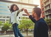 Bekymmerslösa unga par som tillsammans går i stad royaltyfri foto