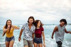 Bekymmerslösa vänner som har gyckel längs stranden royaltyfria foton