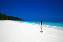 Bekymmerslös lycklig brunettkvinna som går på den tropiska stranden som är exotisk Arkivfoto