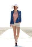 Bekymmerslös ung kvinna som går vid stranden Arkivfoto