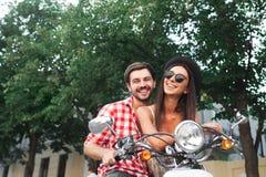 Bekymmerslösa par som har gyckel som rider en sparkcykel Royaltyfri Bild