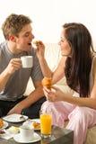 Bekymmerslösa par som äter frukosten i pyjamas Arkivbilder