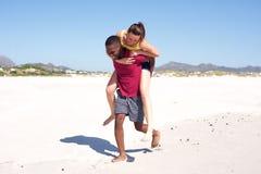 Bekymmerslösa par som tycker om på stranden Royaltyfria Foton