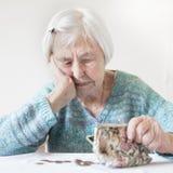 Bekymrad äldre kvinna som sitter på tabellen som räknar pengar i hennes plånbok royaltyfri foto