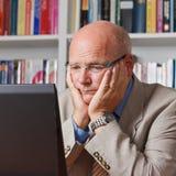 Bekymrad äldre man med datoren arkivfoton