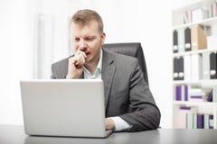 Bekymrad affärsman som arbetar på hans skrivbord Arkivbild