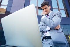 Bekymrad affärsman som ser bärbara datorn royaltyfri foto