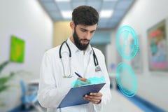 Bekymrad barndoktor med den hållande paperclipen för skägg med medicinska symboler i bakgrund Royaltyfria Foton