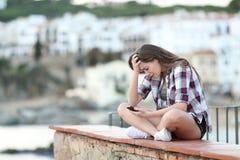 Bekymrad flicka som kontrollerar det smarta telefoninnehållet arkivfoton