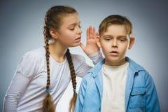 Bekymrad flicka som viskar på den skrämda stressade pojken svart telefon för kommunikationsbegreppsmottagare Fotografering för Bildbyråer